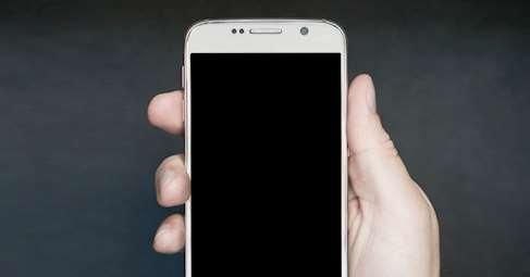Hand som håller i en telefon med en svart skärm.